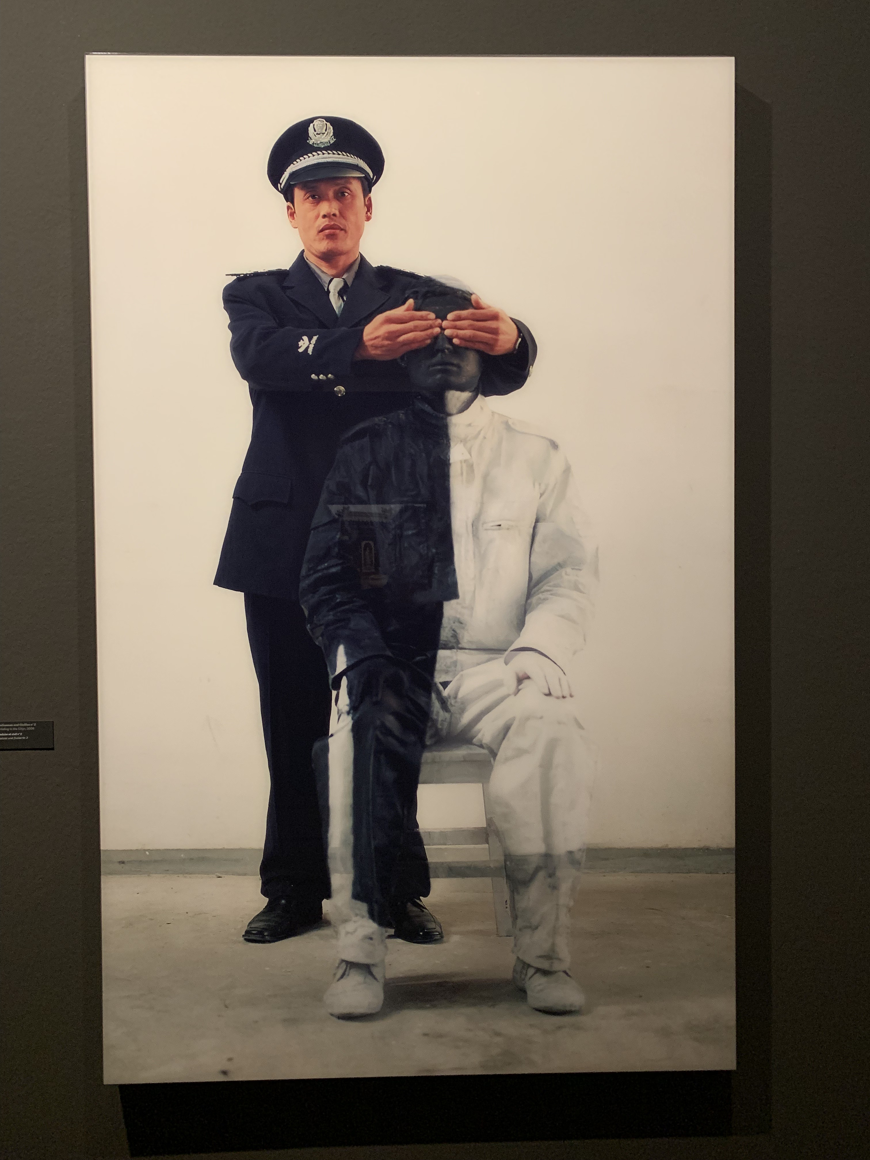 A police officer masking Liu Bolin's eyes