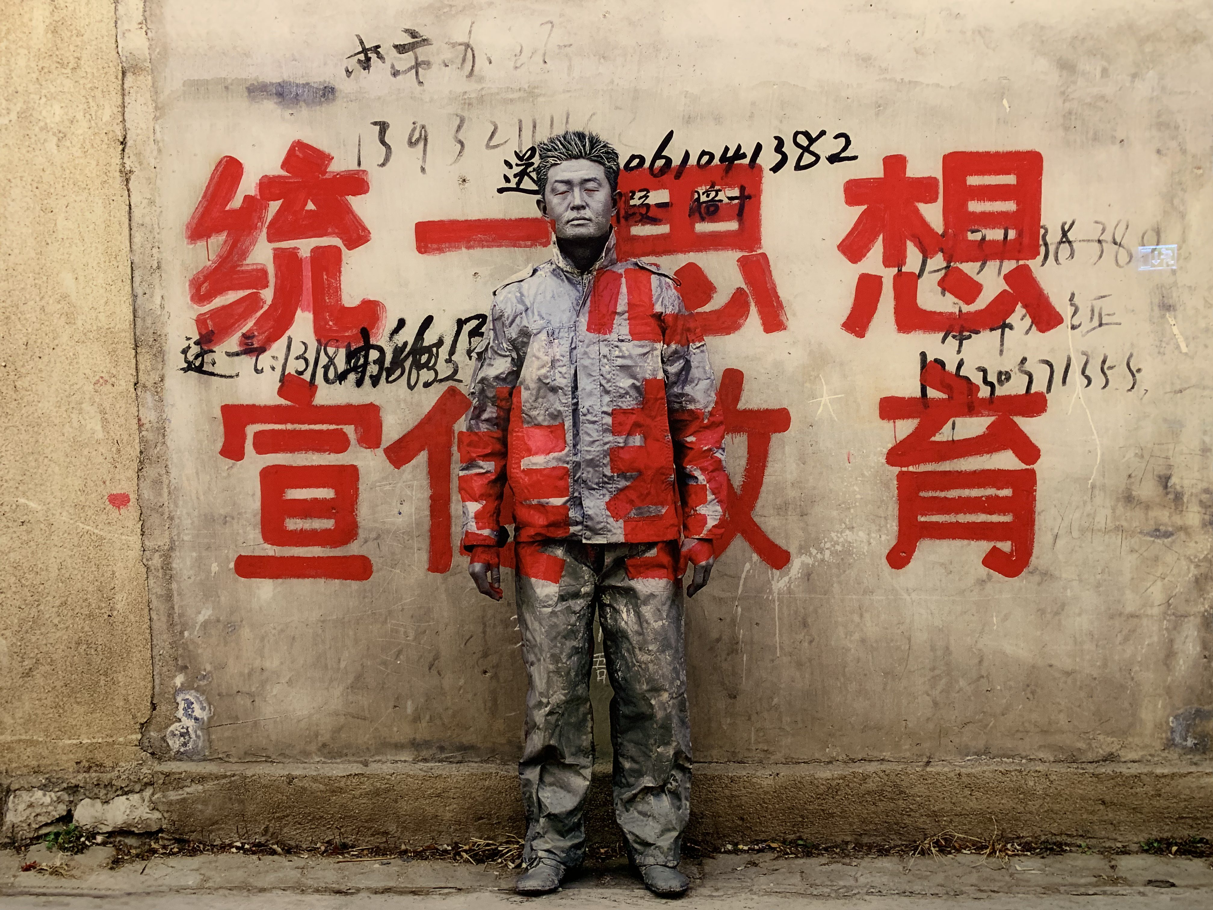 Liu Bolin painted in a wall with graffiti