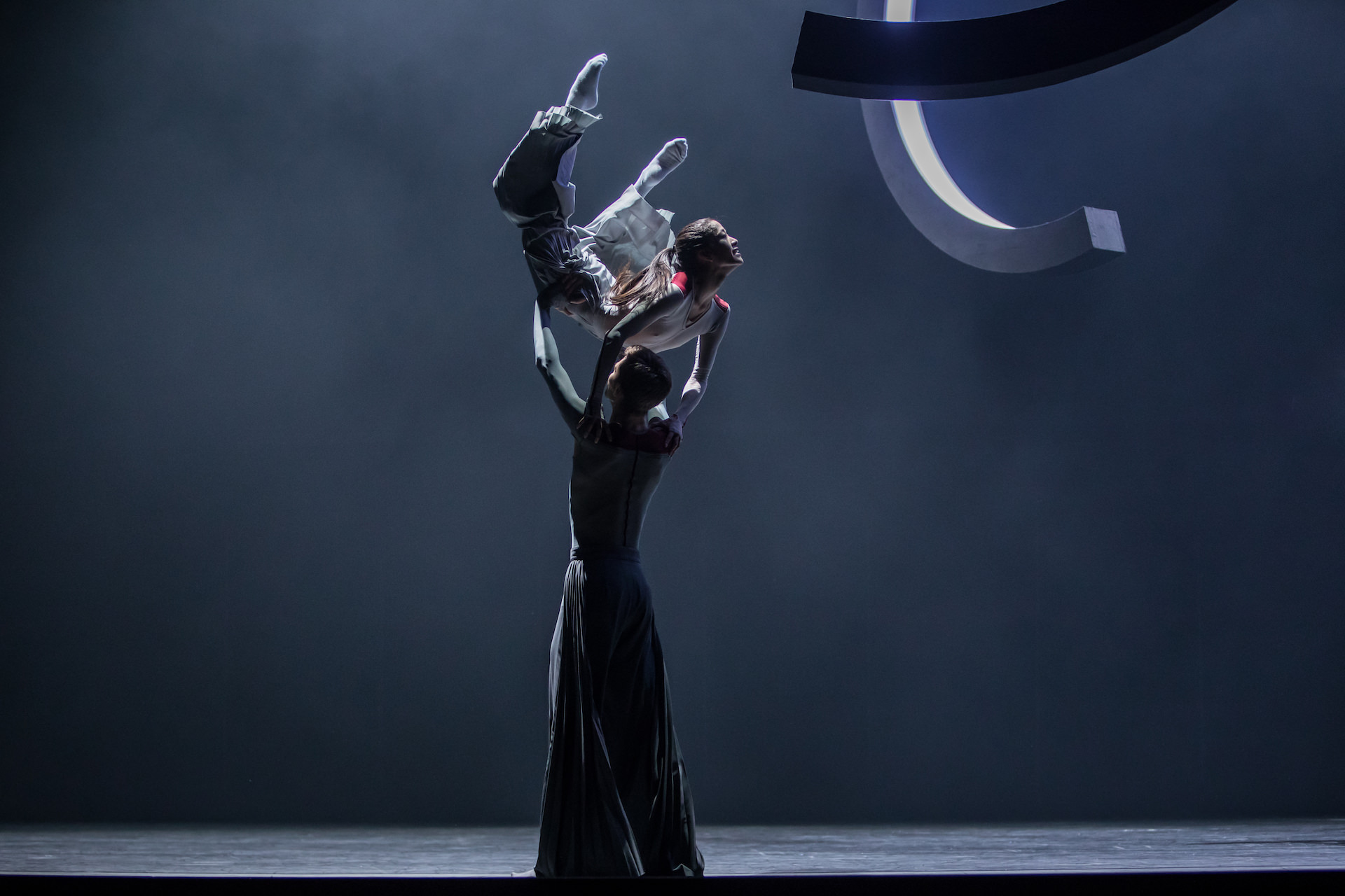 Porté. Male dancer carrying his partner through the stage in a dark grey atmosphere. Photo by Gregory Batardon.